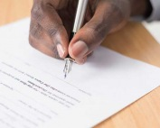 A close-up of a person signing a bail bond agreement at A-Affordable Bail Bonds in Vancouver, WA