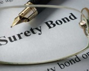A fountain pen and glasses over a surety bond paper highlighting the surety bond and bail bond services by A-Affordable Bail Bonds in Washington State