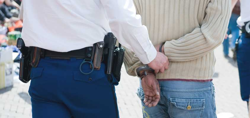 A police officer cuffing a man in jeans and a cream-colored sweater representing the clientele of bail bond agent A-Affordable Bail Bonds in Kelso, WA