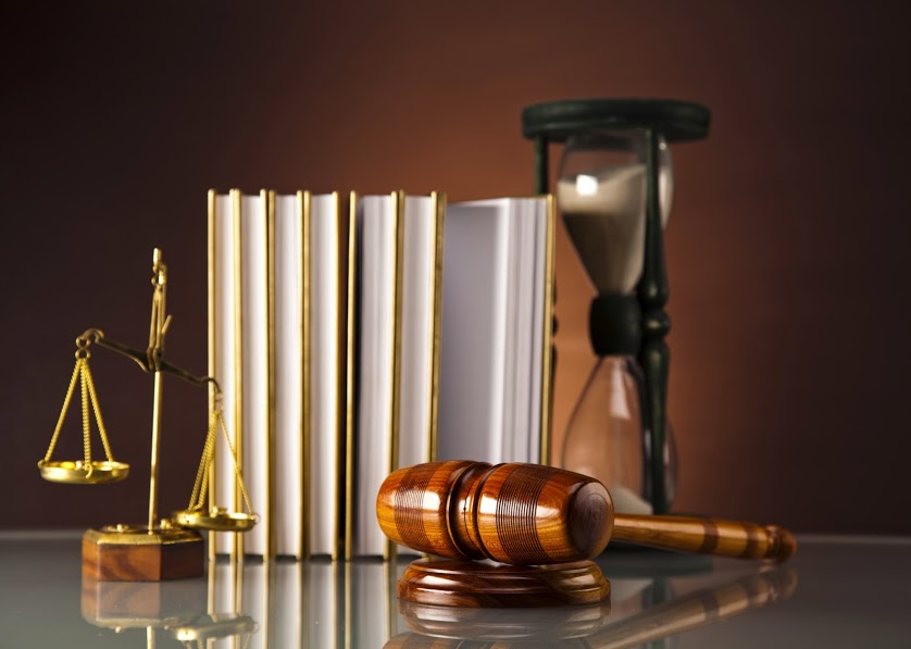 Books, a gavel and a glass timer sitting on a table